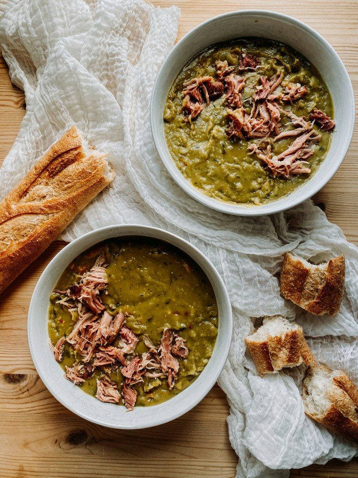 two white bowls silled with Pressure Cooker Split Pea Soup with Smoked Ham Hock resting on a white cloth with French bread on the table