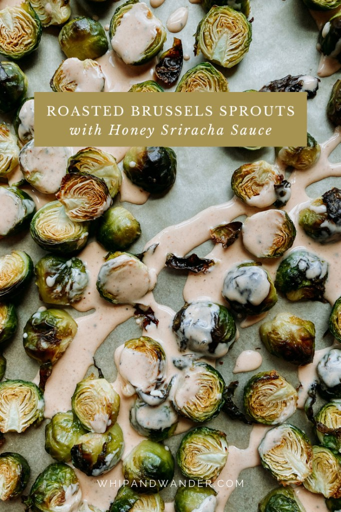 Roasted Brussels Sprouts with Honey Sriracha Sauce resting on a parchment lined bakers half sheet