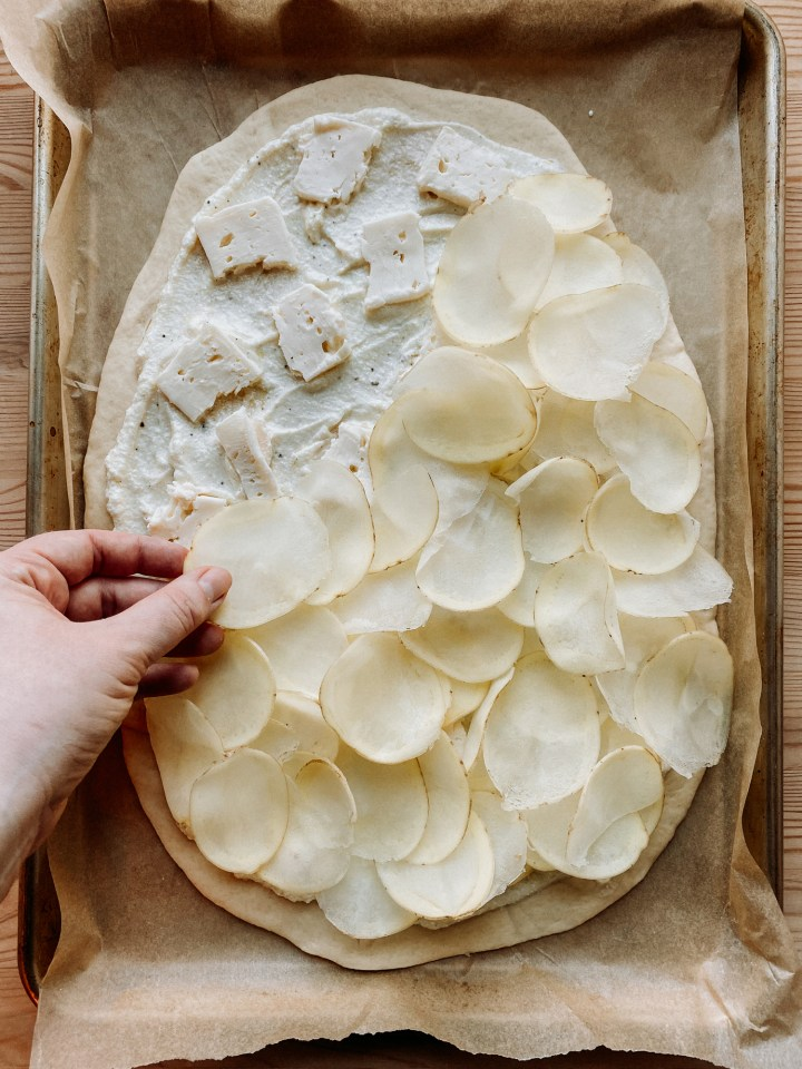 a hand placing slices of potato over the top of a cheese topped pizza