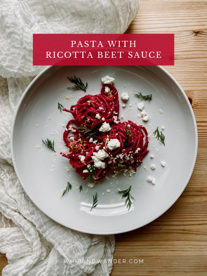 a white bowl with spaghetti noodles coated in beet sauce topped with goat cheese and dill