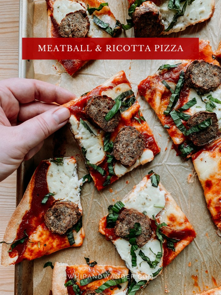 a hand pulling a slice of meatball and ricotta pizza off of a baking tray