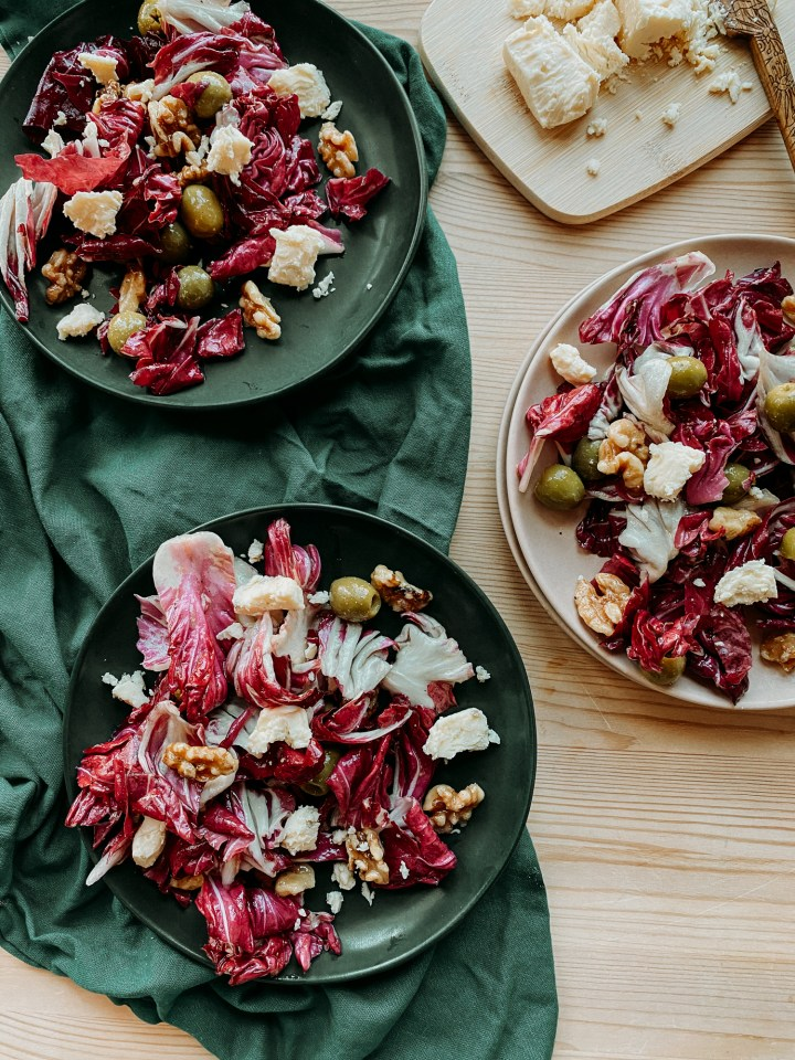 three plates containing Radicchio Salad with Green Olives, Blue Cheese, and Candied Walnuts and a small wooden board with blue cheese resting on a wooden surface with a dark green towel