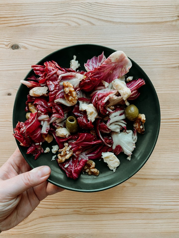 a hand holding a dark green plate with Radicchio Salad with Green Olives, Blue Cheese, and Candied Walnuts over the top of a wooden table