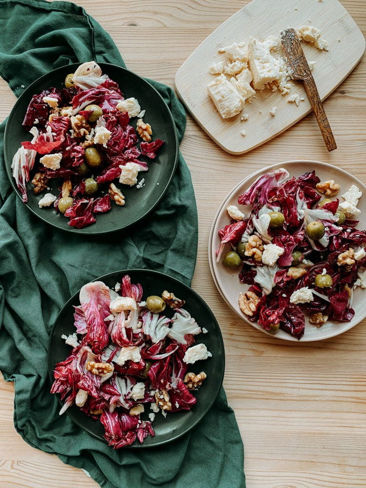 two dark green plates resting on a dark green towel with a light pink plate to the right of them, all with radicchio salad on top