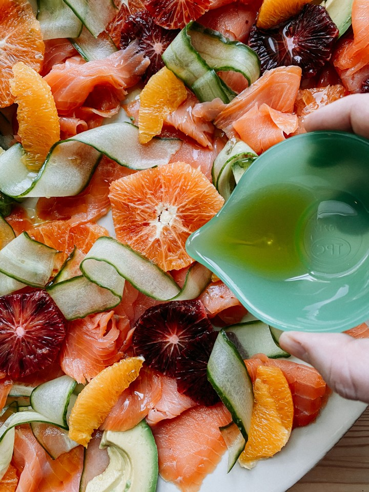 olive oil being poured out of a small green dish over a citrus and salmon salad