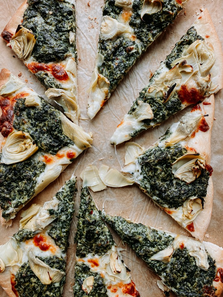 8 slices of spinach artichoke pizza on a baking sheet
