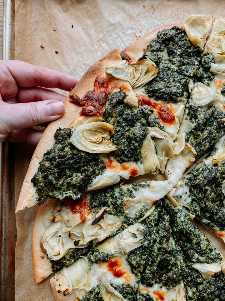 a hand pulling a large slice of spinach artichoke pizza off of a baking sheet