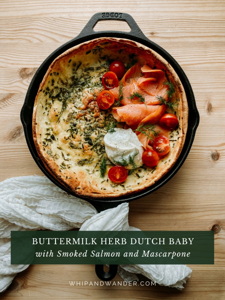 a Savory Buttermilk Herb Dutch Baby topped with smoked salmon in a cast iron pan with a white cloth wrapped around the handle resting on a wooden surface