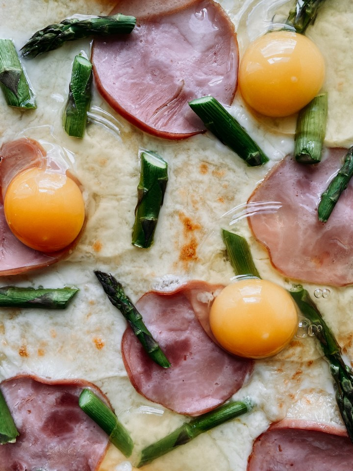 eggs, asparagus, and canadian bacon on a pizza crust that has been par baked