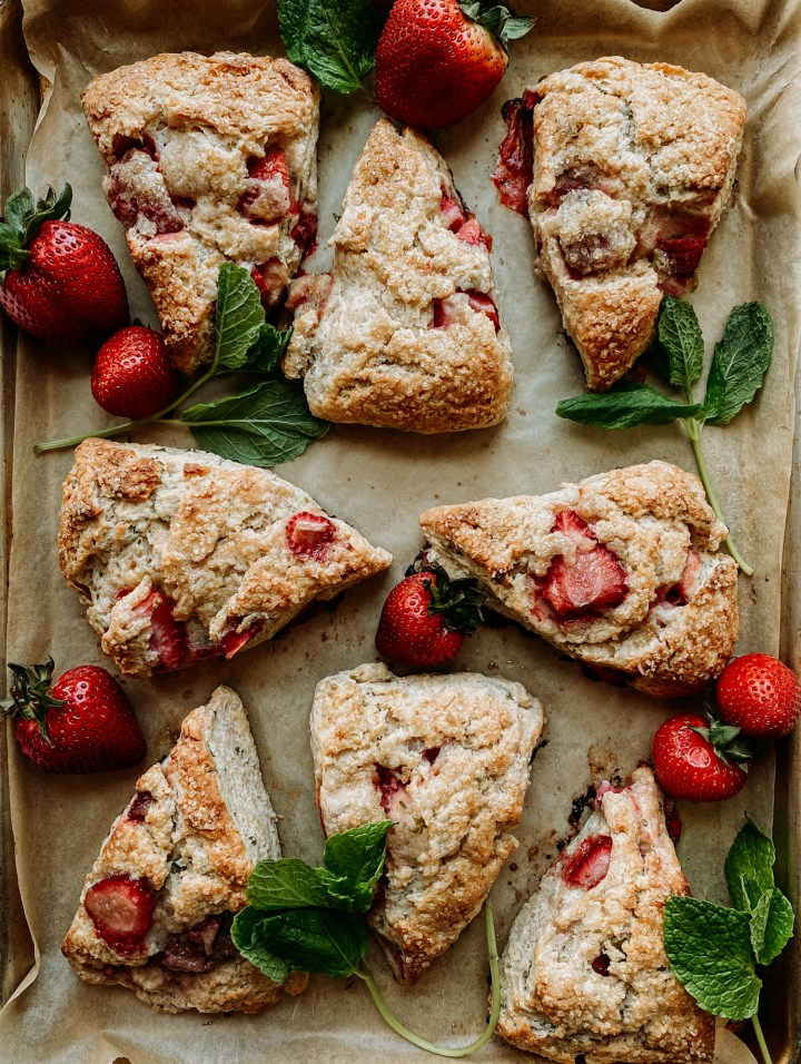 fresh sprigs of fresh mint and fresh strawberries on a baking tray with baked wedges of Sourdough Discard Strawberry Mint Scones