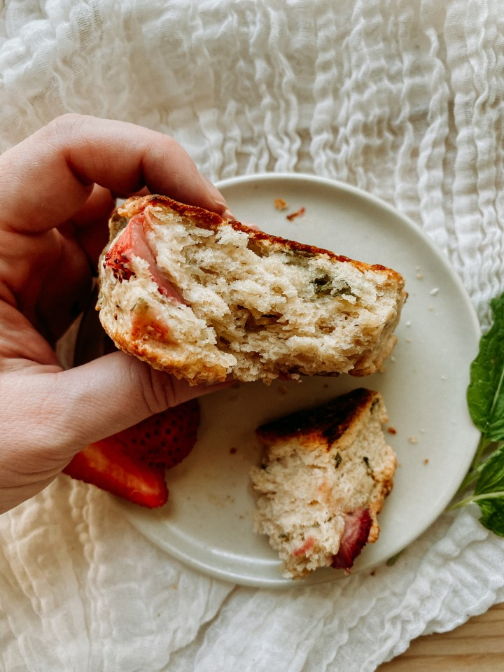 a hand holding a Sourdough Discard Strawberry Mint Scones that has been broken in half to expose the flaky inside texture