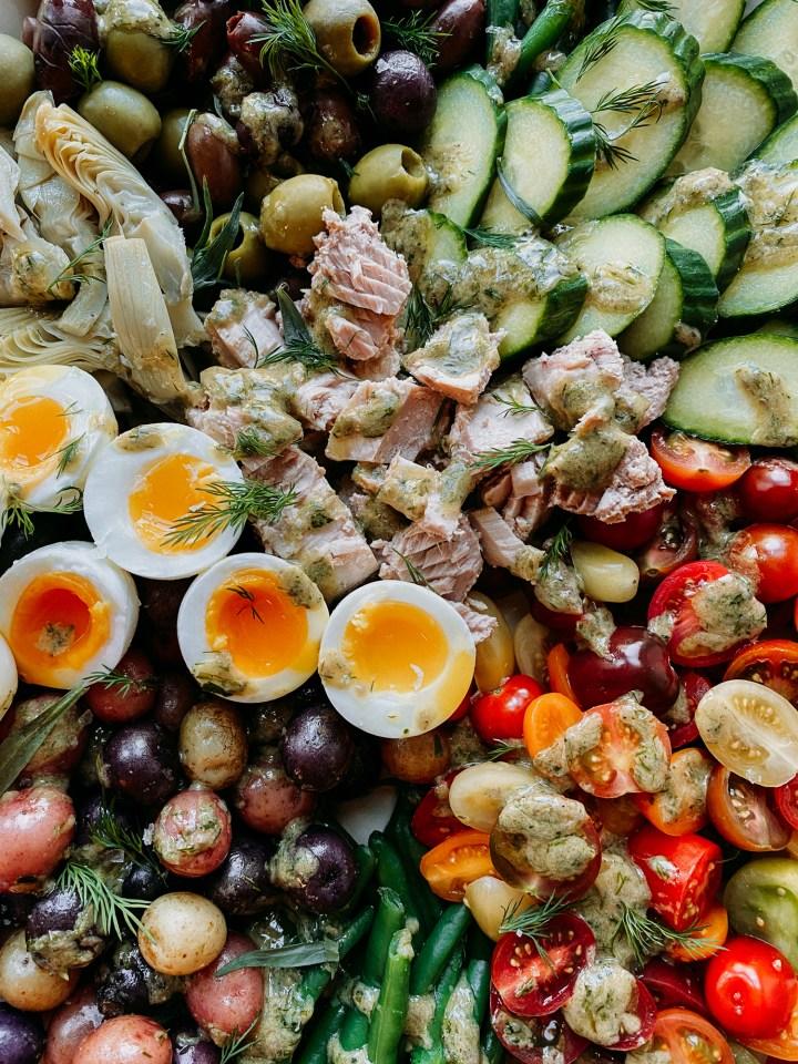 closeup of anchovy dijon vinaigrette on a Tuna Salad Nicoise