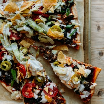 a slice of Taco Pizza pulled away from the whole pizza on a parchment line baking sheet