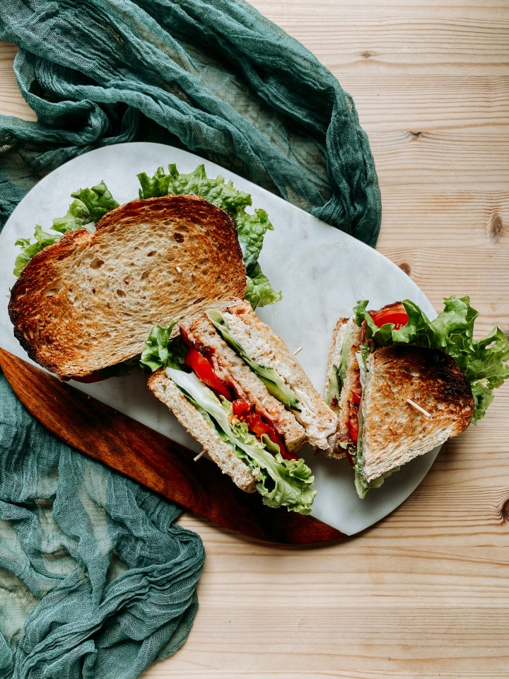 two crab club sandwiches resting on a marble and wood cutting board on a green cloth on a wooden surface