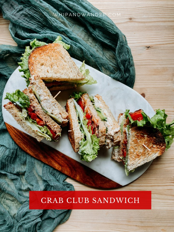 a wooden table with a marble cutting board on top containing crab club sandwiches