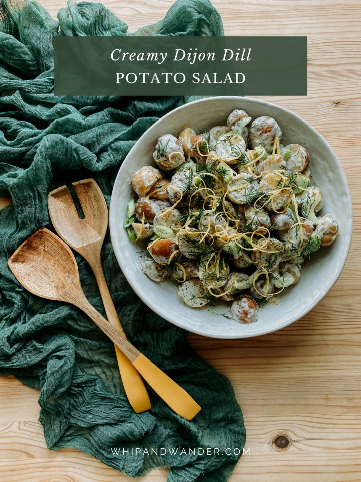 Creamy Dijon Dill Potato Salad in a large white serving bowl resting on a green cloth with yellow tipped wooden salad servers resting nearby