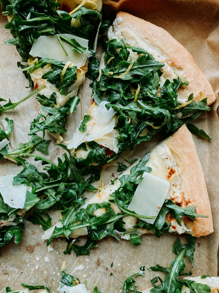 Pizza Bianca (White Pizza) slices topped with parmesan arugula salad