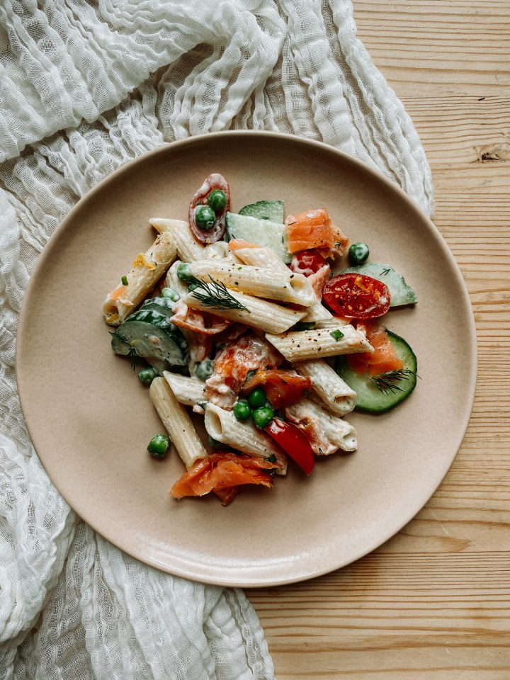 a pink plate with smoked salmon pasta salad resting on a white cloth of a wooden table