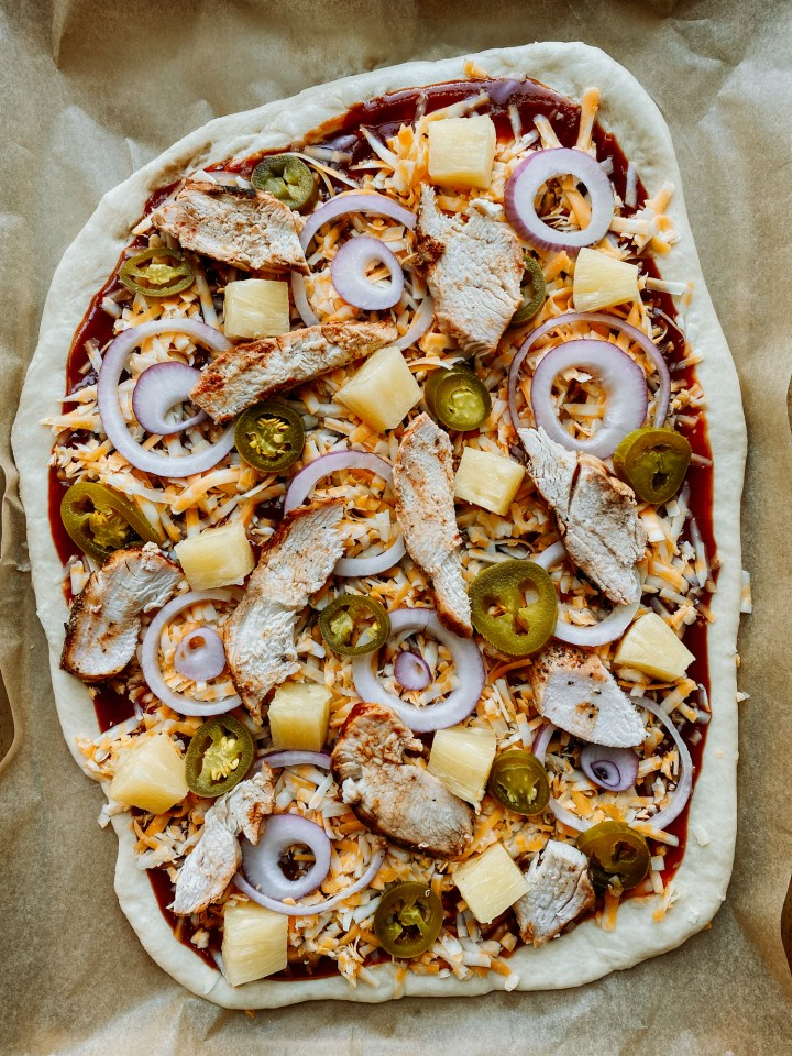 an unbaked BBQ Chicken Pizza resting on a baking sheet