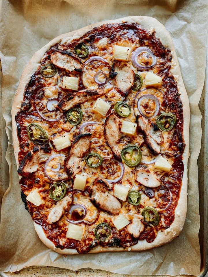 a baked BBQ Chicken Pizza resting on its baking sheet