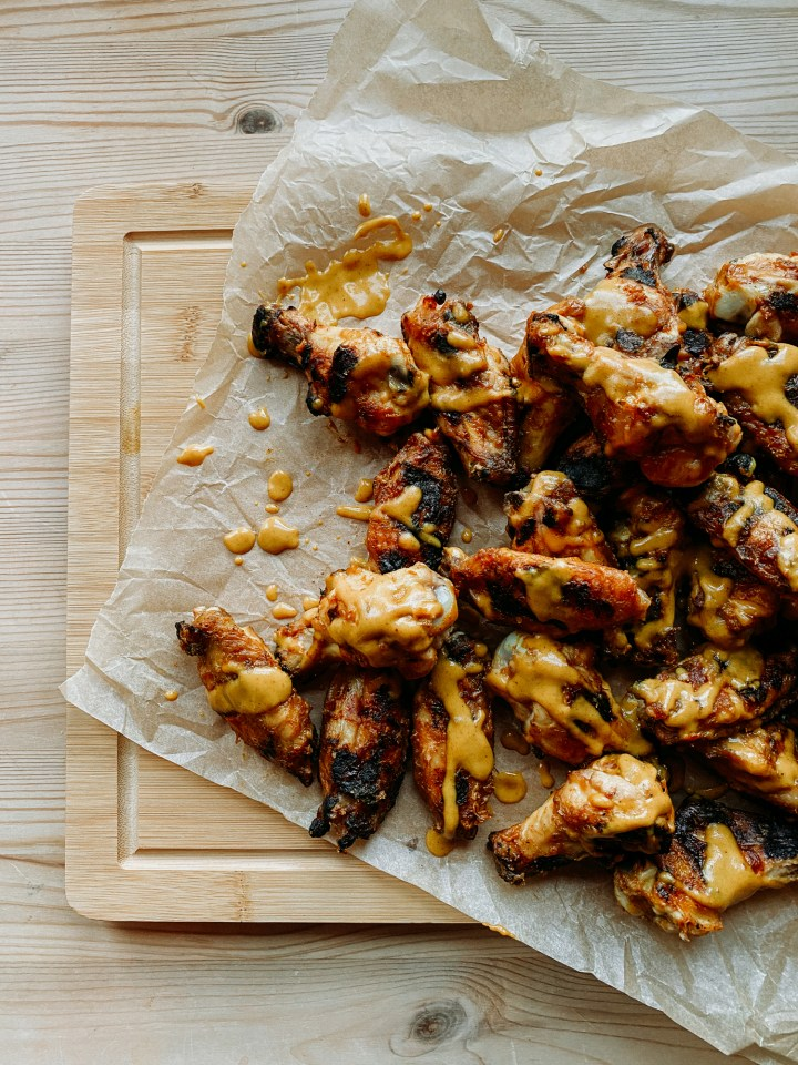 a cutting board covered with chicken wings