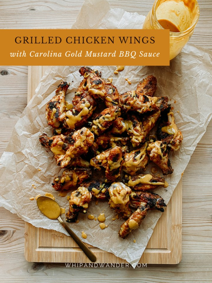 chicken wings that have been grilled resting on a wooden cutting board
