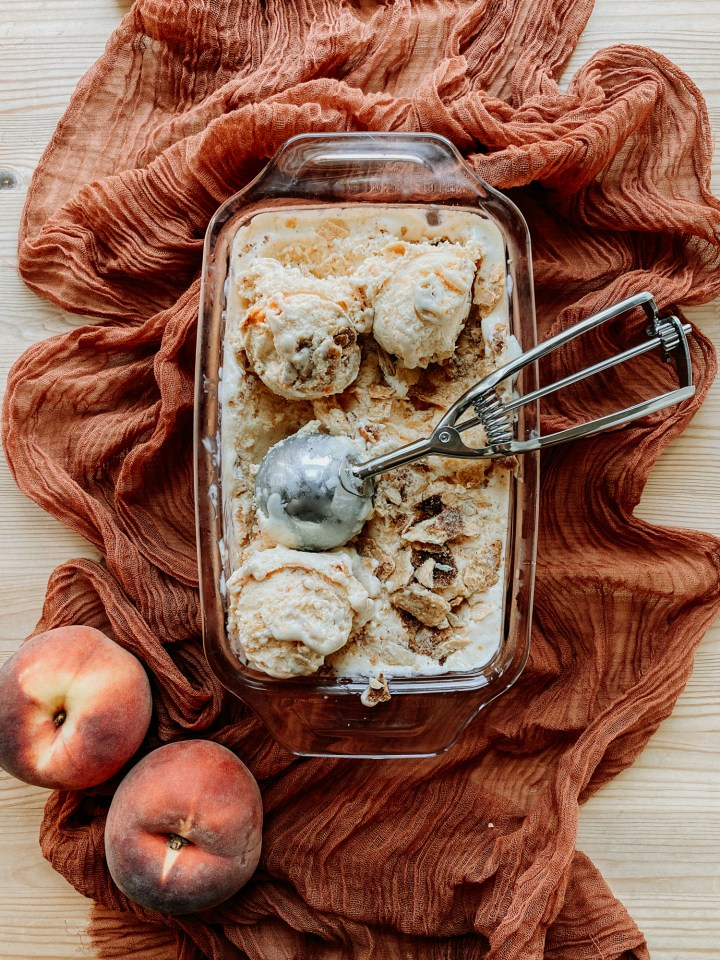 Buttermilk Peach Pie Ice Cream in a pink glass loaf pan resting on a dark peach colored cloth with a metal ice cream scoop in the pan