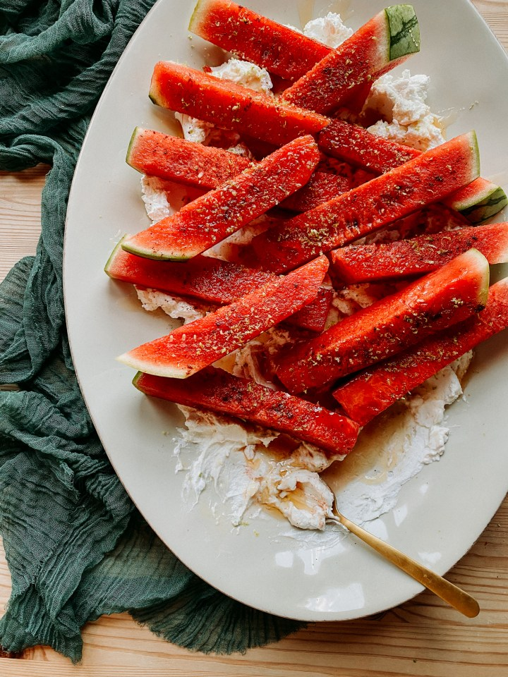 a gold spoon resting in honey and labneh on a platter with chili lime watermelon