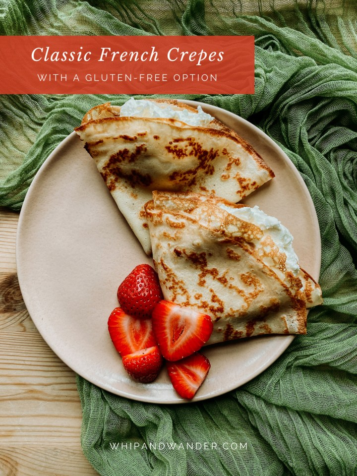 strawberries on top of cream filled french crepes on a pale pink plate on a green cloth