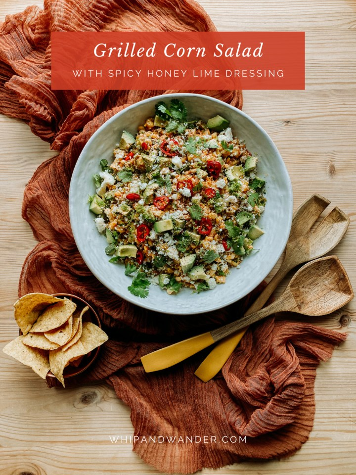 wooden serving utensils and a bowl of tortilla chips resting next to a white dish filled with Grilled Corn Salad with Spicy Honey Lime Dressing