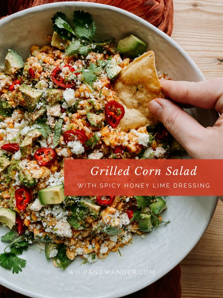 a hand using a tortilal chip to scoop grilled corn and pepper salad