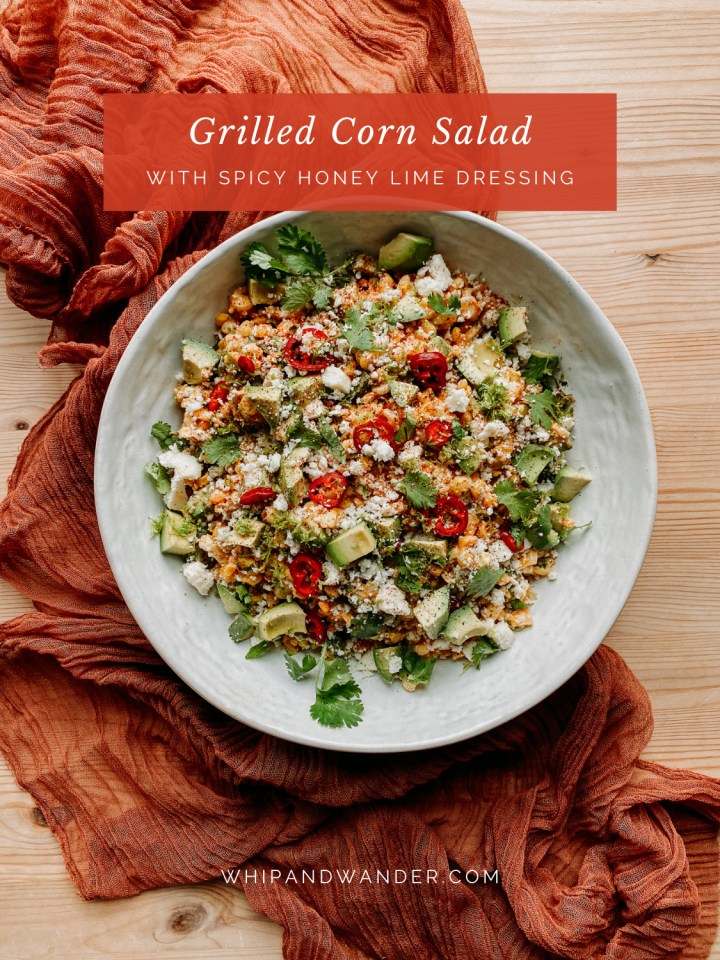 a white dish filled with Grilled Corn Salad with Spicy Honey Lime Dressing resting on a dark orange red cloth on a wooden table