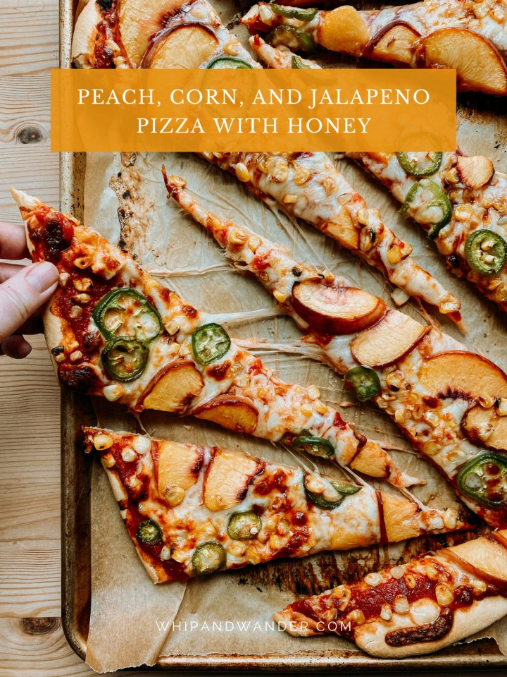 a hand grabbing a slice of corn, jalapeno, and peach pizza off of a baking sheet