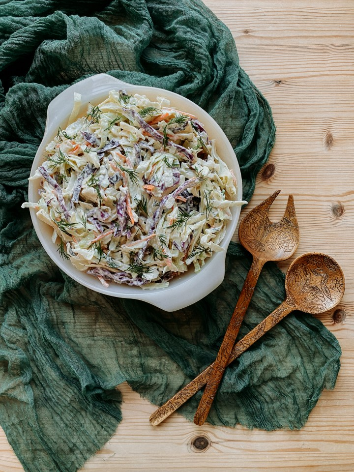 Horseradish Dill Slaw in a glass serving bowl on a dark green fabric cloth with wooden serving utensils resting nearby