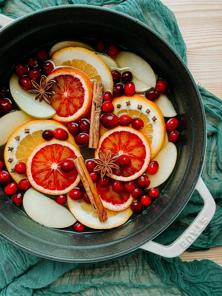 slices of apples, navel and blood oranges, cranberries, cinnamons ticks, cloves, and star anise, and apple cider in a large white dutch oven