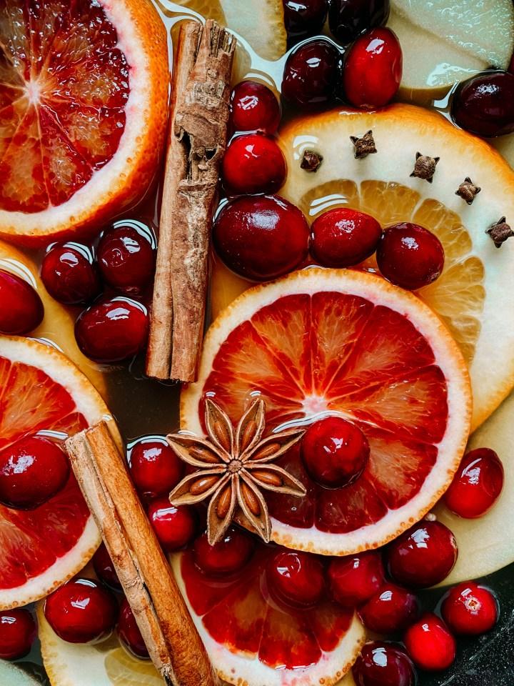 sliced blood oranges, navel oranges, cloves, cranberries, star anise, and cinnamon sticks