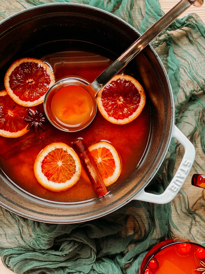 a white dutch oven pot filled with apple cider, sliced oranges, and cinnamon sticks