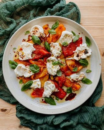 Roasted Pepper and Burrata Salad ona. large round white platter on top of a dark green cloth