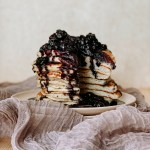 Blueberry sauce ont op of a stack of pancakes that have been cut into resting on a lilac cloth