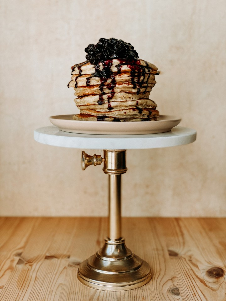 pancakes with blueberry sauce stacked on a pink plate on a cake stand