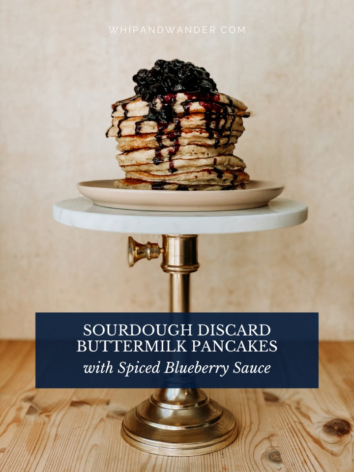 a stack of pancakes toped with spiced blueberry sauce resting on a pink plate on top of a cake stand