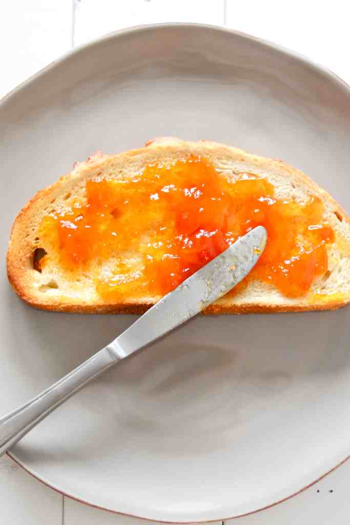 apricot preserves spread on a piece of sourdough bread