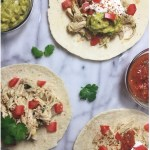 Slow-cooker cilantro lime chicken tacos on a marble board with salsa and guacamole