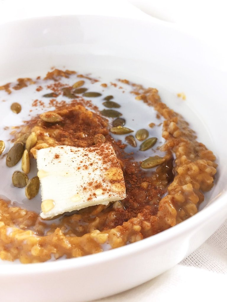 A closeup of a white bowl of pumpkin spice steel cut oatmeal with milk, butter, cinnamon and pepitas, from the side, on a white cloth napkin.