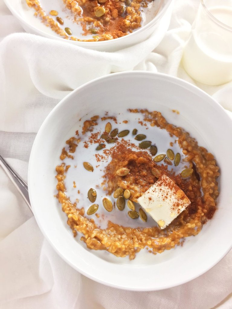 A white bowl of pumpkin spice steel cut oatmeal with milk, butter, cinnamon and pepitas beside a milk cup on a white cloth napkin.