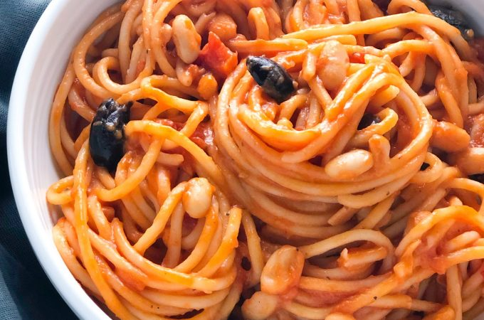 Pasta in tomato sauce with olives and white beans in a white bowl