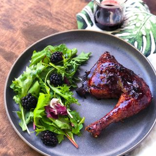 Black Raspberry Glazed Chicken Legs with blackberry salad on a gray plate, on a white tea towel with green leaves.