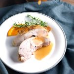 Gravy being poured onto slices of roasted turkey breast on a white plate with an orange slice and herbs. A jar of gravy is in the background