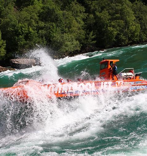 orange open jet boat in class v rapids
