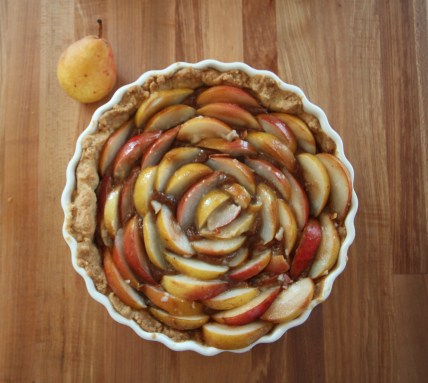 An unbaked fig pear tart rests on a wooden surface; a lone pear rests beside the tart. The pears are arranged in concentric circles, and you can see some fig puree peeking from beneath them.